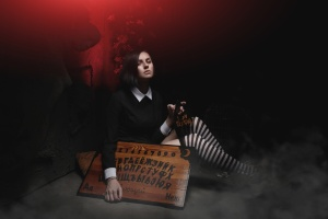 beautiful school girl witch tells fortunes and speaks with ghosts with spiritual board
